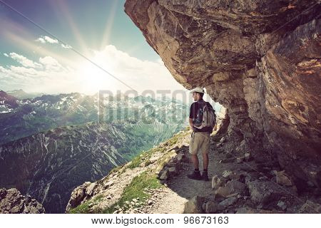 Backpacker standing in the shade under a rocky overhang looking out over the alps at the Hochvogel, Germany with a bright sunburst on the horizon poster