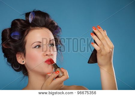 Young woman preparing to party girl styling hair with curlers applying makeup red lipstick retro style blue background poster