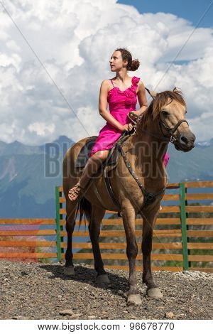 woman in evening dress on horseback in the mountains