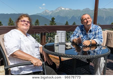 elderly couple at a table on the balcony in the mountains