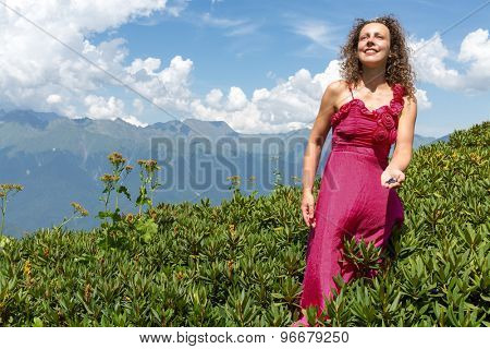 woman in evening dress gathering berries in the mountains