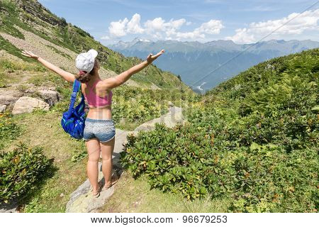 woman raises her arms to the sky in the mountains