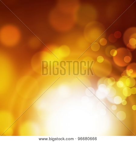 Abstract blurred bokeh background in yellow gold brown colors with white light effect