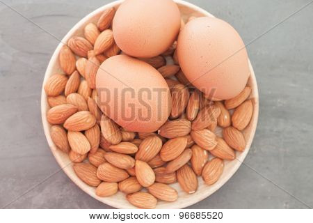 Almond Nuts And Eggs On Wooden Plate