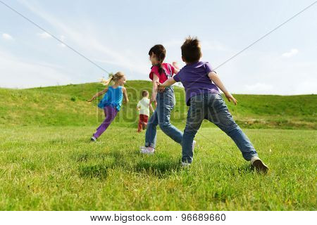 summer, childhood, leisure and people concept - group of happy kids playing tag game and running on green field outdoors