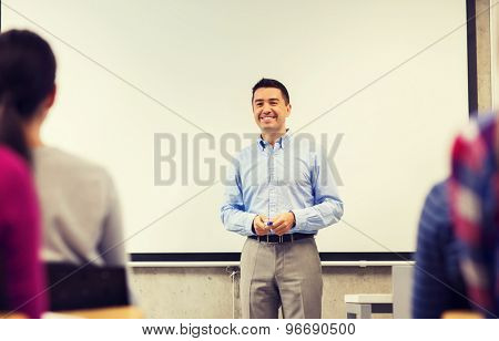 education, high school, teamwork and people concept - smiling teacher standing in front of white board and students in classroom