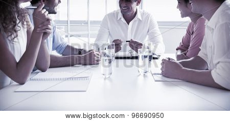 Smiling business people in meeting at conference table in office