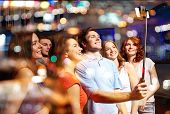 party, technology, nightlife and people concept - smiling friends with smartphone and monopod taking selfie in club poster