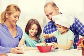 food, family, children, hapiness and people concept - happy family with two kids making dinner at home poster