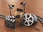 Video movie cinema concept. Light film strip reels rails clapperboard and director chair on the wood background. poster