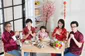 Happy Chinese New Year, reunion dinner. Happy Asian Chinese multi generation family with red cheongsam greeting while dining at home. poster