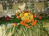 Wedding top table centerpiece, made of yellow, orange and red daisies and roses and green aspidistra. poster