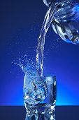 Water poured into a glass, splash, blue background, refreshing, freshness and health. Water bottle, water pitcher, blue liquid, ice, drops, motion, wave, splash, transparency blue liquid on water bottle or pitcher, ice, drops. Gradient background. poster