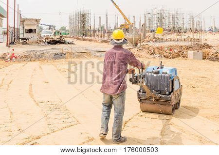 Construction workers during road roller at work on the road construction. Manual labor on construction site.
