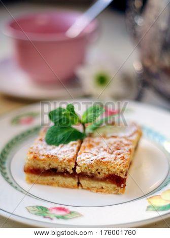 Tasty grated tart with jam of a porcelain plate. Food, dessert, sweet, jam, cake, mint,