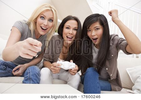Three beautiful interracial young women friends at home having fun playing computer games together and laughing