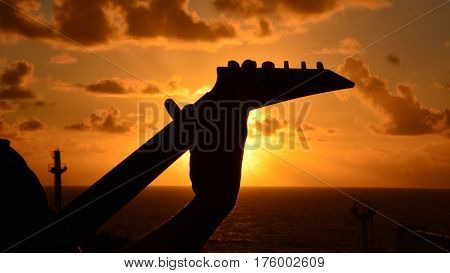 A silhouette of guitar on sunrise sky background