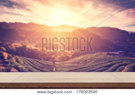 Empty Wooden Table For Product Placement Or Montage And Blurred Tea Field And Sunrise Vintage.