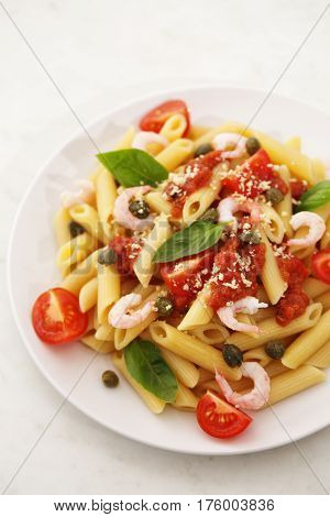 Penne alla vodka pasta in tomato sauce with shrimp and capers on a white plate
