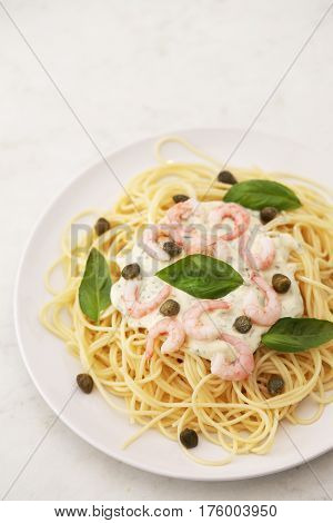 spaghetti with white sauce and shrimps and capers on a white plate