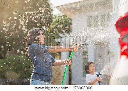 Asian children washing car in the garden on summer day