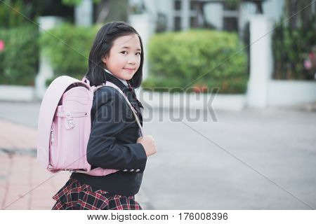 Beautiful Asian school girl with pink backpack outdoorsback to school concept