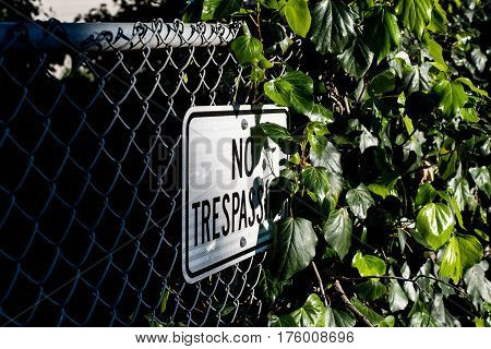 No trespassing sign hanging on chain link fence