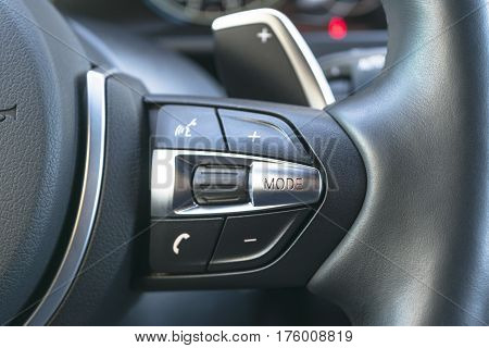 Hands free and media control buttons on the steering wheel in black leather modern car interior