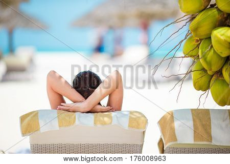 Beautiful woman relax on the beach near big coconuts