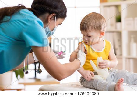 Female doctor makes a vaccination to a child