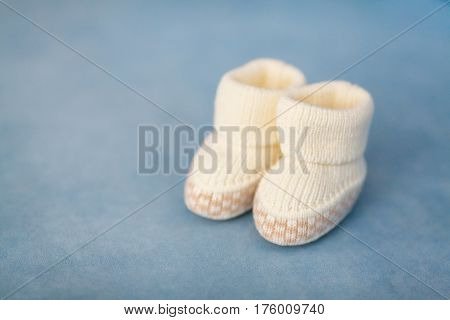 White crochet baby booties on blue background closeup selective focus