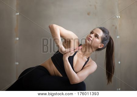 Young attractive yogi woman practicing yoga, standing in Parivrtta Parsvakonasana exercise, Revolved Side Angle pose, working out, wearing black sportswear, cool urban style, grey studio, portrait