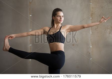 Portrait of young woman practicing yoga, standing in Parivrtta Utthita Hasta Padangusthasana exercise, Twisting Extended Hand to Big Toe pose, wearing black sportswear, cool urban style, grey studio
