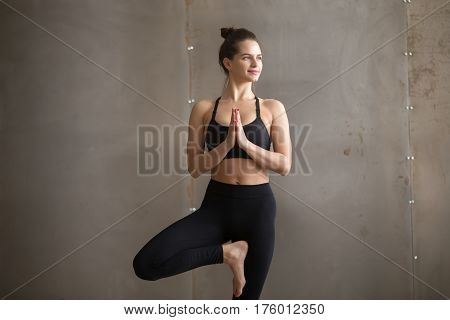 Portrait of young smiling attractive yogi woman practicing yoga, standing in Vrksasana exercise, Tree pose, working out, wearing black sportswear, cool urban style, grey studio background, closeup
