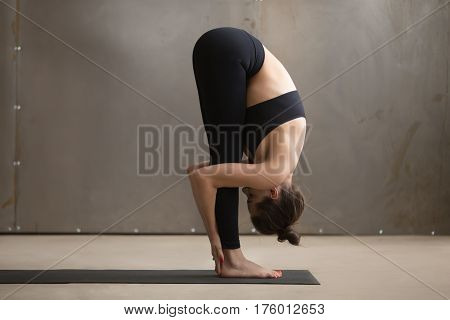 Young attractive woman practicing yoga, standing in head to knees, uttanasana exercise, Standing forward bend pose, working out, wearing black sportswear, cool urban style, full length, grey studio