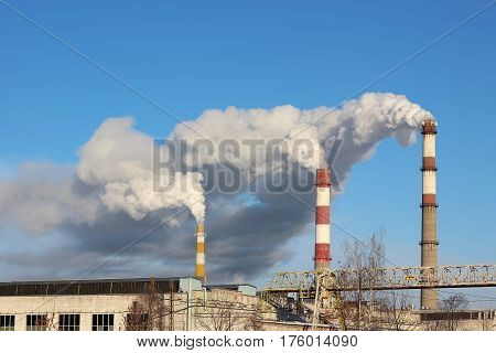 Dense clouds of smoke or vapor out of the three factory chimneys on background of blue sky. The concept of ecology pollution of the environment.