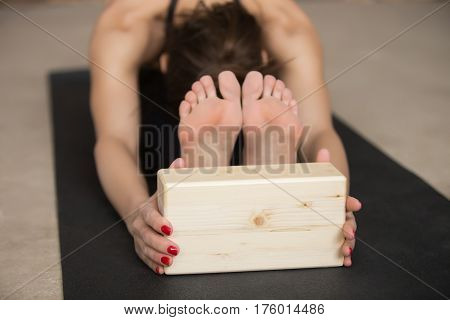 Young attractive woman practicing yoga, stretching in paschimottanasana exercise, using wooden block, Seated forward bend pose, wearing black sportswear, working out on the studio floor, close up
