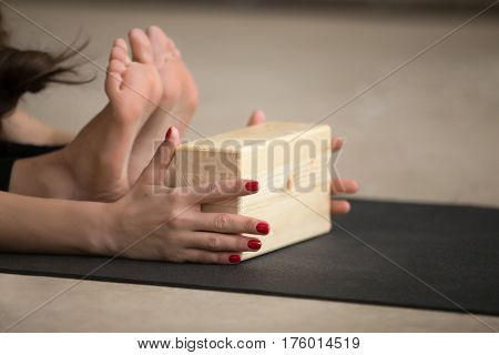 Young sporty yogi woman practicing yoga, stretching in paschimottanasana exercise, using wooden block, Seated forward bend pose, working out on grey studio floor, close up, short red manicure
