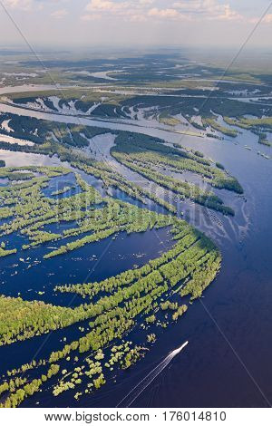 Aerial view flooded forest plains. Rapid motor boat moves on the river.
