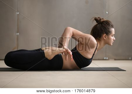 Young attractive yogi woman practicing yoga, stretching in Bhekasana exercise, Frog pose, working out, wearing black sportswear, cool urban style, full length, grey studio background, side view
