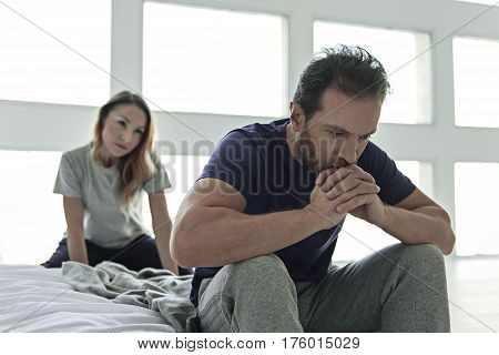 Frustrated husband is on bed. Anxious looking wife behind him