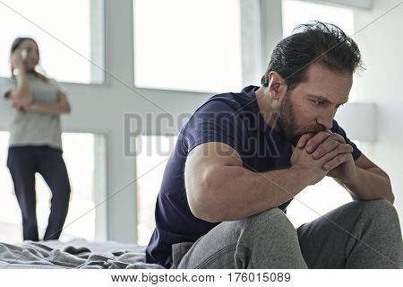 Despaired male person sitting on bed and looking dowm. His wife is standing and touching her face after fight on background
