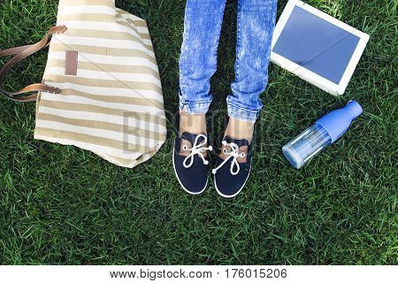 Feet of a young girl on a background a green grass with bottle of tablet computer water and bag. Travel and holliday concept