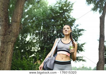 Young happpy woman walking in the park after sport activity with detox drink