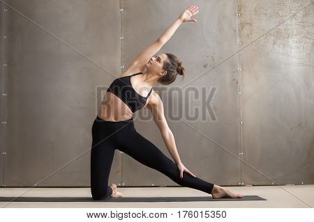 Full length portrait of young attractive woman practicing yoga, stretching in Parighasana exercise, Gate pose, working out wearing black sportswear, cool urban style grey studio background, front view