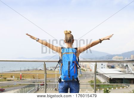 Happy blond woman from behind with arms outstretched