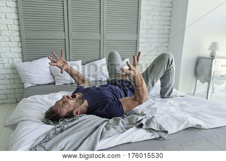 Furious male person is frantically yelling. He lying at disassembled bedstead