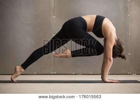 Young attractive woman practicing yoga or pilates, standing in Bird dog pose, Knee to Forehead curl exercise, working out wearing black sportswear, cool urban style grey studio background, full length