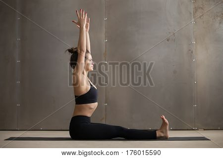 Young attractive yogi woman practicing yoga, sitting in Dandasana exercise, Staff pose, working out, wearing black sportswear, cool urban style, full length, grey studio background, side view
