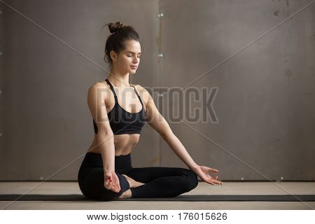 Young attractive sporty yogi woman practicing yoga, sitting in Sukhasana exercise, Easy Seat pose, working out wearing black sportswear, cool urban style grey studio copy space background, full length